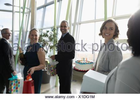 Heureux les gens d'affaires exerçant son gâteau d'anniversaire et cadeaux in office Banque D'Images