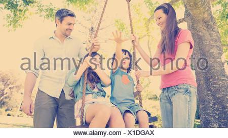 Heureux couple poussant kids on swing Banque D'Images