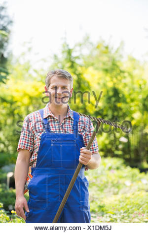 Portrait of confident gardener holding rake in plant nursery Banque D'Images