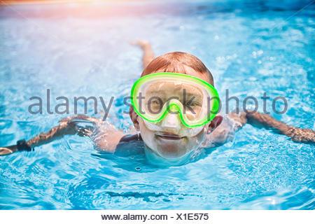 Portrait of boy wearing green masque de plongée en piscine piscine ensoleillée Banque D'Images