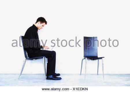 Homme assis sur un fauteuil avec un ordinateur portable Banque D'Images