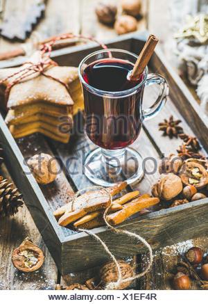 Verre de vin chaud en plateau en bois avec Noël gingerbread cookies, les noix, la cannelle, l'anis et des pommes de pin rustique en bois plus Banque D'Images