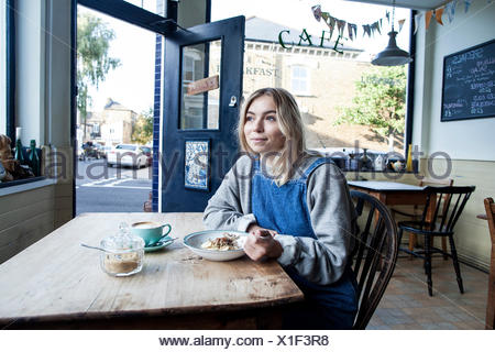 Young woman in cafe, manger du muesli