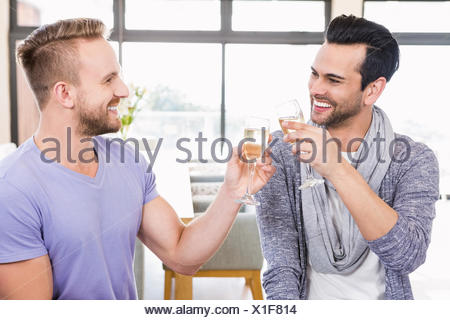 Smiling gay couple toasting with champagne Banque D'Images