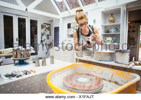 Un potter de la manipulation d'un pot d'argile humide, la préparer pour la cuisson au four.
