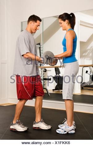 L'homme et la femme la levée de poids dans une salle de sport Banque D'Images