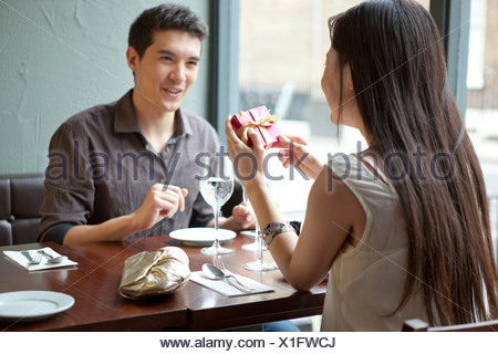 Young couple in restaurant, woman holding gift box Banque D'Images