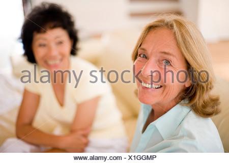 L'amitié. Deux femmes friends chatting sur un canapé à la maison. Banque D'Images