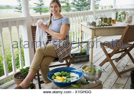 Portrait de femme assise par fresh cucumbers in bowl Banque D'Images