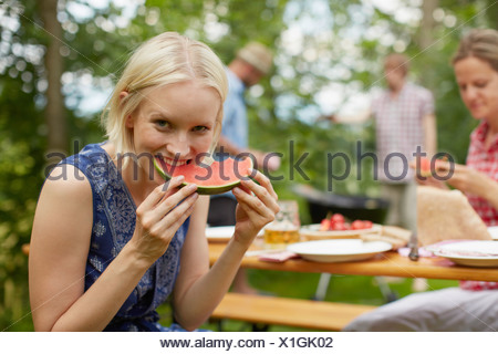 Woman eating watermelon outdoors Banque D'Images
