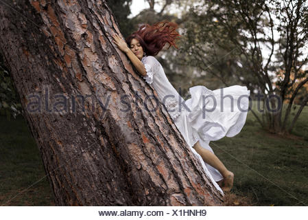 Belle femme embrassant un arbre