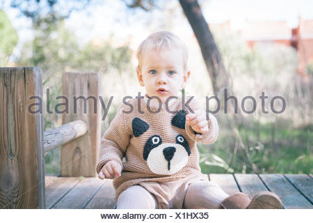 Garçon assis sur une structure construite en jeu pour enfants