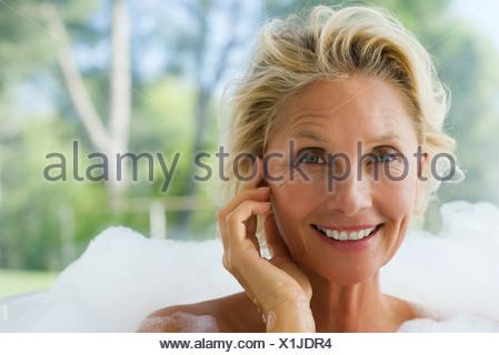 Mature Woman relaxing in bubble bath, portrait Banque D'Images