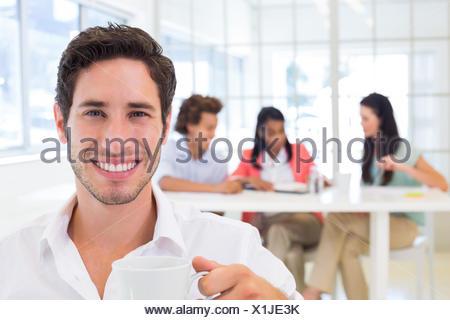 Businessman drinking hot beverage Banque D'Images
