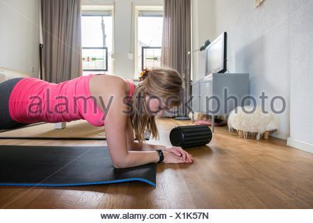 Tilburg, Pays-Bas. Les jeunes adultes girly femme travaillant à l'intérieur de son salon. Banque D'Images