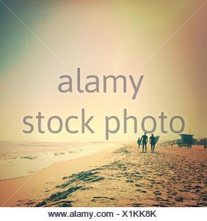 Silhouette de surfers walking along beach Banque D'Images