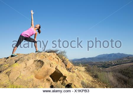 Woman practicing yoga posent sur hill, Thousand Oaks, Californie, USA Banque D'Images