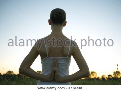 Woman doing yoga pose, les mains jointes derrière le dos, au coucher du soleil Banque D'Images