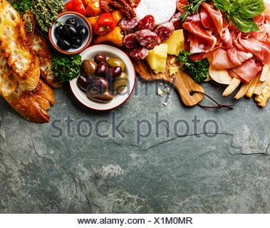 Ingrédients alimentaires italien de fond avec jambon, salami, parmesan, olives, bâtonnets de pain sur ardoise en pierre Banque D'Images