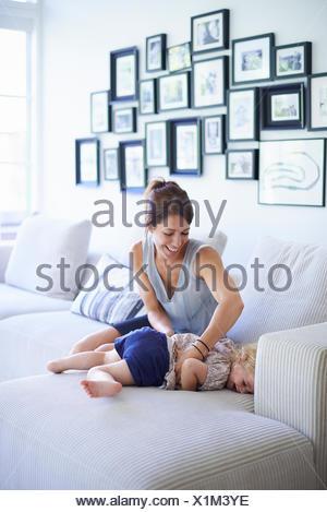 Mid adult mother chatouillant toddler fille sur canapé Banque D'Images