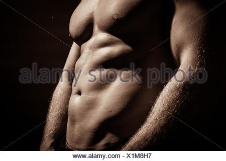 Au milieu du torse nu musclé homme debout sur fond noir Banque D'Images