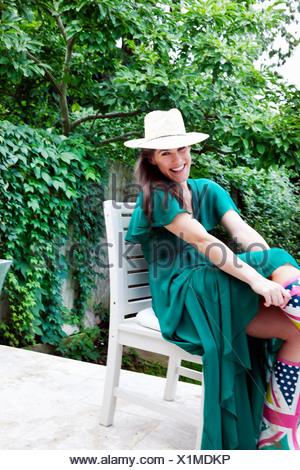 Jeune femme portant robe vert et un chapeau assis sur une chaise de jardin