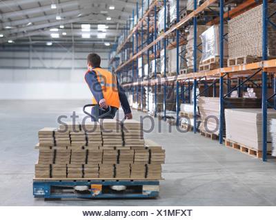 Le transport des travailleurs dans l'entrepôt de charge Banque D'Images