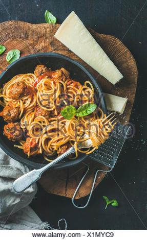 Dîner de pâtes italiennes. Spaghetti avec meatballas, basilic et parmesan en plaque noire sur fond de bois rustique foncé, vue du dessus, Slow food concep Banque D'Images