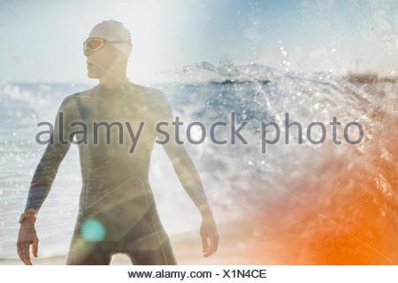 Un nageur dans un wet suit debout au bord de l'eau. Banque D'Images