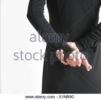 Vue arrière d'une femme avec les doigts croisés derrière retour Banque D'Images