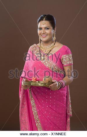 Portrait d'une femme en sari holding offrande religieuse