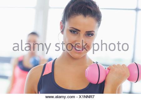 Woman lifting dumbbell poids avec ami en arrière-plan at gym Banque D'Images