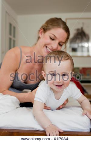 Directeurs mère baby boy crawling on bed Banque D'Images