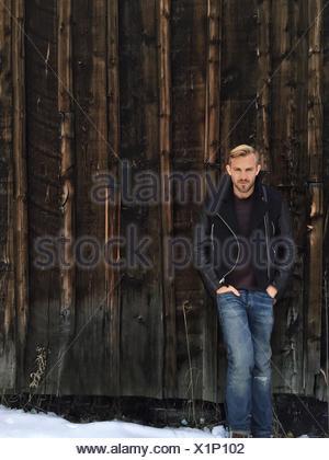 Full Length Portrait of Young Man Standing On Snowy Landscape contre mur en bois Banque D'Images