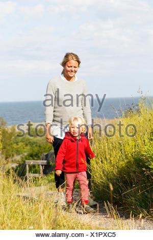 La Suède, l'archipel de Stockholm, Sodermanland, Oja, Woman walking with son (2-3) le long chemin à travers l'herbe verte Banque D'Images