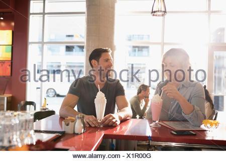 Jeune couple drinking milkshakes à diner counter Banque D'Images