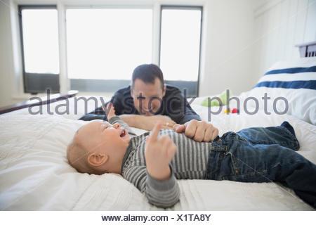 Père et fils baby laughing on bed Banque D'Images