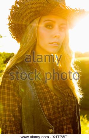 Femme portant un gilet et chapeau de paille Banque D'Images