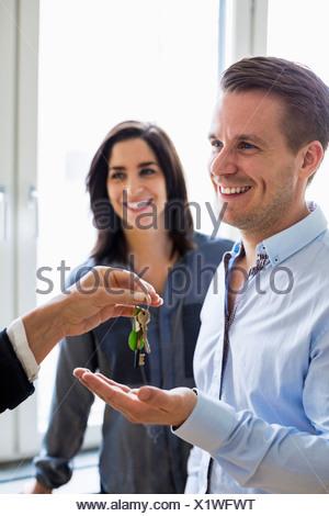 Portrait d'agent immobilier à la remise des clés couple in new house Banque D'Images