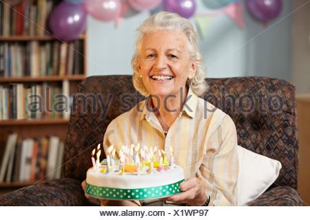 Senior woman holding birthday cake, portrait Banque D'Images
