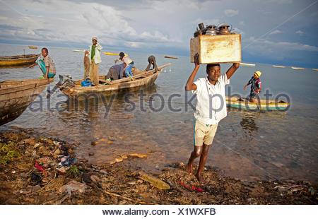 Un garçon portant un fort avec des lampes à l'huile de bateau de pêche, le lac Tanganyika, le Burundi, Makamba, Mvugo, Nyanza Lac Banque D'Images