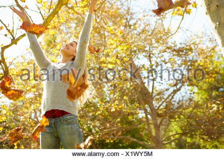 Woman Throwing les feuilles d'automne dans l'air