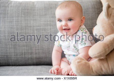 Baby Girl (12-17 mois) avec teddy bear sitting on sofa Banque D'Images