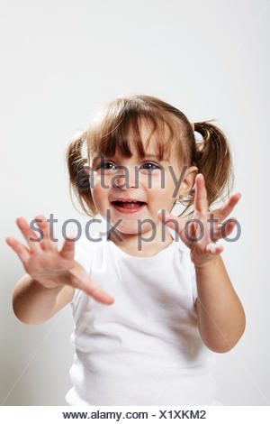 Portrait de jeune fille avec des nattes, avec hands up Banque D'Images