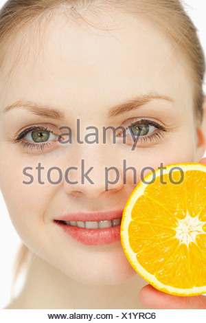 Gros plan d'une femme passant une orange sur ses lèvres Banque D'Images