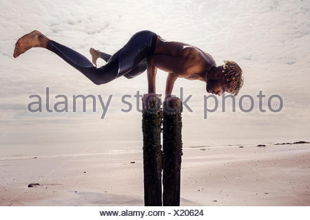 Jeune homme, formation doing handstand sur plage en bois posts Banque D'Images