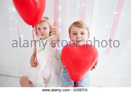 Jeune garçon et fille posant pour une photo dans un studio de photographes, holding red balloons. Banque D'Images