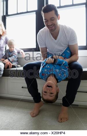 Père Fils rire tenant à l'envers Banque D'Images