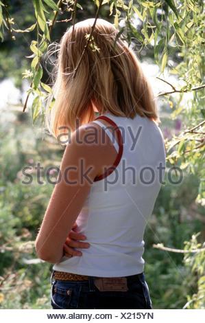 Vue arrière jeune femme anonyme seul à l'extérieur debout, les bras croisés. Banque D'Images