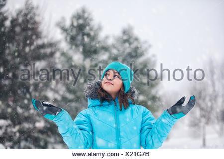 Turquoise Girl wearing Knit hat et manteau, bras levés, les mains hors de la neige, de la capture à la up smiling Banque D'Images